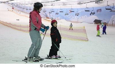Mother with daughter stand on ski and talk - Mother with her...