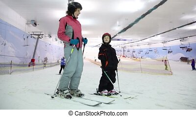 Mother with daughter stand on ski and talk