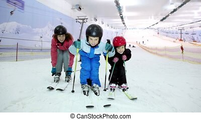 Mother with her kids stand on ski and sway at background of...