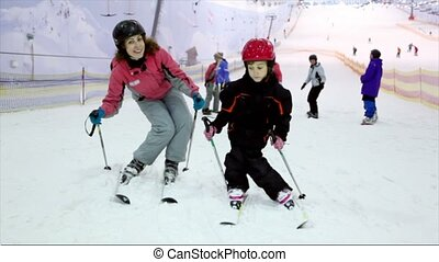 Mother with her little daughter stand on ski and sway -...