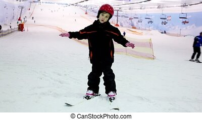 Little girl stands on ski and swings at background of snow slope and ropeway