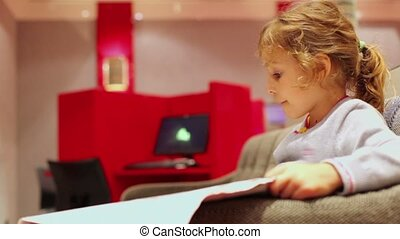 Little girl sits in chair and reads newspaper at room with...