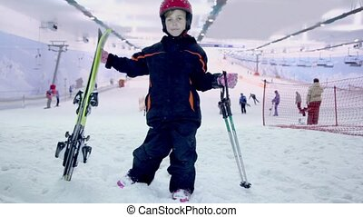 girl stands with ski and poles at background of snow slope