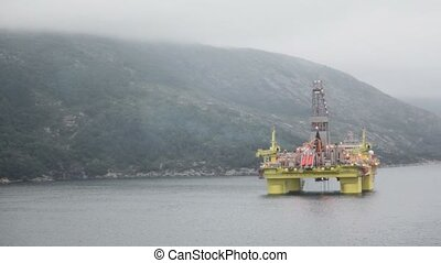 Oil rig located in sea near mountain on shore under cloudy sky