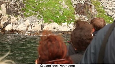 Heads of tourists on ship which stand near coast at fiord