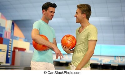 Two friends stand in bowling club with balls and talk