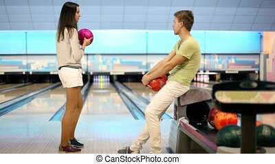 Girl throws bowling ball and boy raises hands satisfied with result