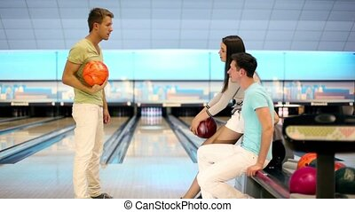 Boy with girl watch how their friend throws bowling ball and...