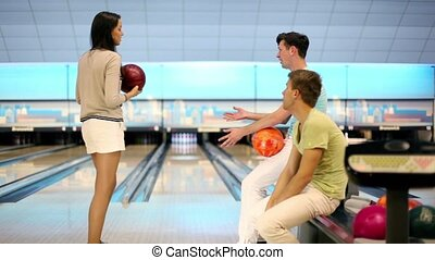 Two boys watch how girl makes throw in bowling game with...