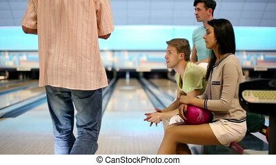 Students team watch how man beats last skittle by bowling...