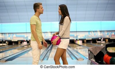 Bow with girl speak and smile near bowling lane in club