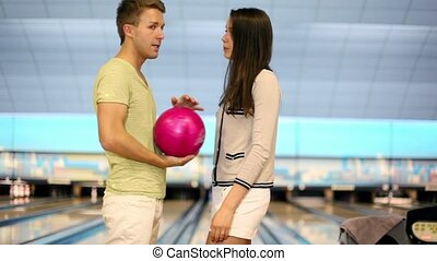 Two students stand and talk near bowling lane in club