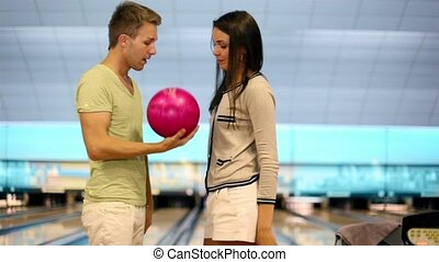 Young couple speak and smile near bowling lane in club and...