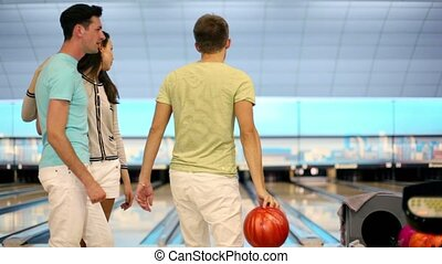 couple watch how friend makes good throw in bowling game -...
