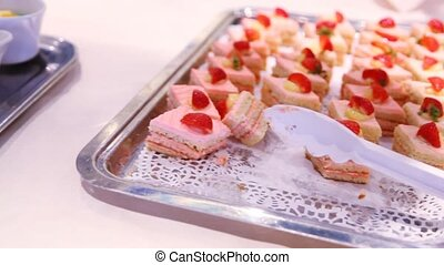 Small cakes stands on white tray on table in dishes