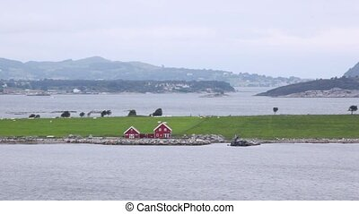 Two red houses stands on bank of gulf in Stavanger