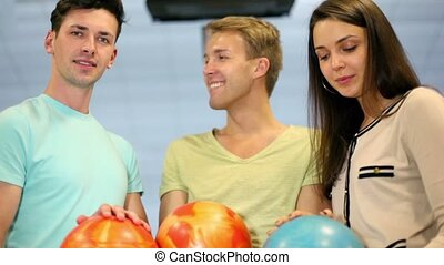 Two boy and one girl hold bowling balls and smile, closeup view