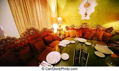 Near table there are three sofas with pillows in east style