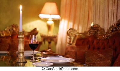 Wineglass with red wine stands on table near burning candle