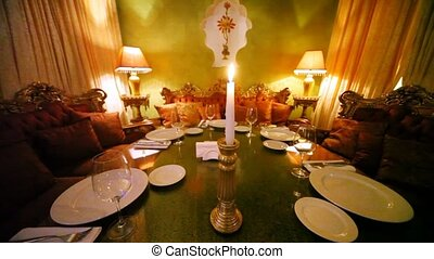 candle stands on decorated table among subjects of east decor