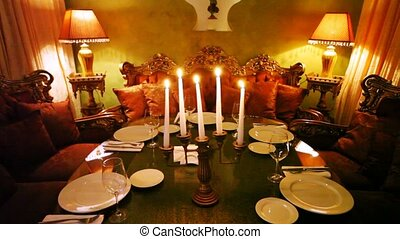 Candlestick decorates table and supplements decor of restaurant