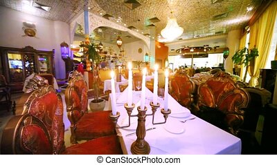 Lounge of restaurant is located behind candlestick with candles