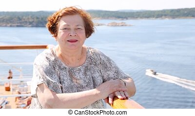 Attractive older woman stands on ship deck in afternoon