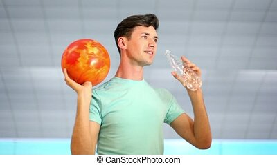 Young man hold bowling ball and drink water from plastic bottle