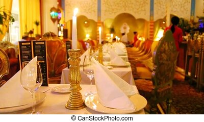 Tables stand  in center of hall of restaurant with candles