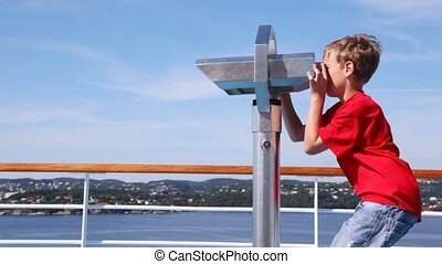 Boy looks in binocular on ship deck against blue sky and...