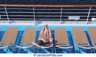 Mother with daughter lie in chaise lounge on liner deck