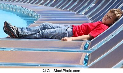 Boy sleeps in chaise lounge on ship deck in afternoon