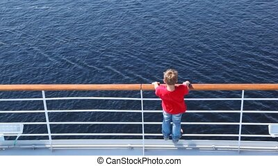 Boy looks at water standing on ship deck in afternoon