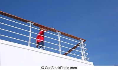 Boy waves greeting by hand standing on ship handrail against blue sky
