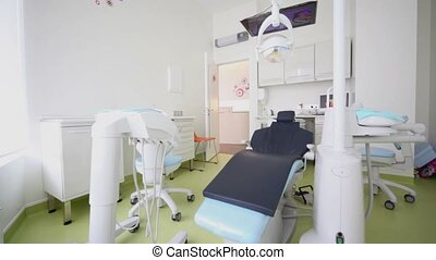 Room of dental surgery with tv set above chair and other...