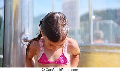 Nice little girl washes under water in shower cabin