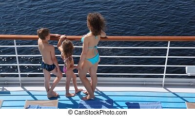 Mother, daughter and son look at water on board ship