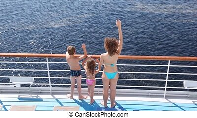 Mother, daughter and son stands waving hands on board ship