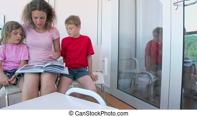 Woman reads book with two her kids at balcony on ship -...