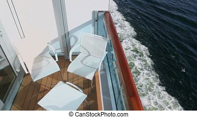 Furniture at balcony on vessel which floats in sea, gulls...