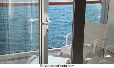 Door to balcony with furniture on vessel which floats in sea