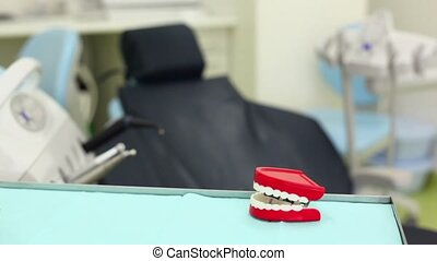 Big toy jaw knacks his teeth on table in dental surgery