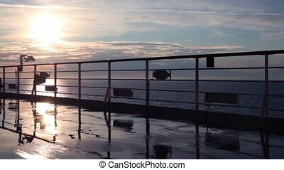 Silhouette of woman walks by deck near fence and watch sunset under sea during cruise
