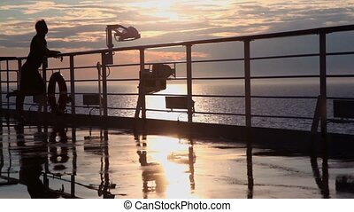 Silhouette of woman watch sunset and walk away from deck of...
