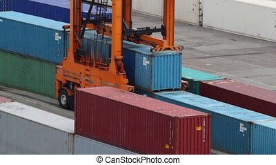 Reachstacker lifts one of several containers in port at day
