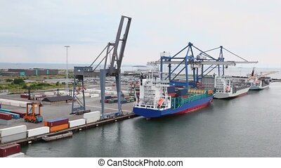 Shipment of cargo in containers to barges by huge cranes and...