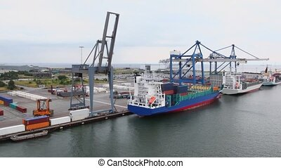 Embarkation of barges by huge cranes and reachstackers in dock