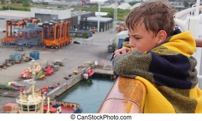 Boy with damp hair and covered by plaid stand on deck of ship