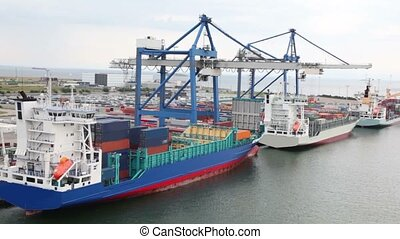 Several barges on embarkation by huge cranes in dock at...