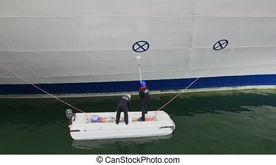 Two workers stand on small boat and paint board of huge ship